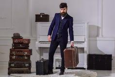 行李交付概念 强壮男子典雅在严密的面孔站立近的堆葡萄酒手提箱,拿着手提箱 人 库存图片