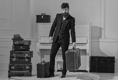 行李交付概念 强壮男子典雅在严密的面孔站立近的堆葡萄酒手提箱,拿着手提箱 人 库存照片