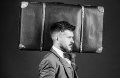 行李保险 旅行和行李概念 带着大手提箱的人穿着考究的有胡子的行家 采取所有您的事 库存照片