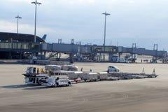 行李卡车转移行李到钾的机场 免版税库存照片