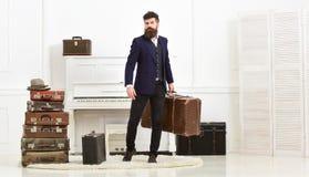 行李和假期概念 强壮男子典雅在严密的面孔站立近的堆葡萄酒手提箱,拿着手提箱 人 免版税库存图片