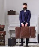 行李和旅行的概念 强壮男子时髦在严密的面孔站立并且运载大葡萄酒手提箱 人,旅行家 免版税库存照片