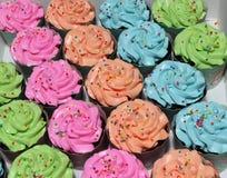 行橙色,蓝色,绿色和桃红色杯子蛋糕用五颜六色的被环绕的糖在奶油成串珠状 免版税库存照片
