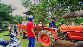 滑行车周围拖拉机的人们有拖车的在村庄 股票录像