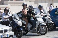 滑行车的人们在城市交通 免版税库存图片