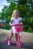 滑行车的快乐的逗人喜爱的小女孩在公园 库存图片