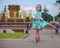 滑行车的快乐的逗人喜爱的小孩女孩在a 图库摄影