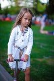 滑行车的美丽的小孩女孩在公园 库存照片