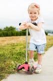 滑行车的逗人喜爱的小女孩 免版税图库摄影