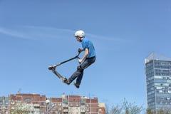 滑行车轻碰的男孩在天空中 免版税库存照片