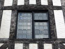 行间空格特别大的玻璃窗在一个半木料半灰泥的房子里 图库摄影