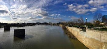 街市城市地平线印第安纳波利斯印第安纳怀特河在有开花的树的春天和植被、步行桥和废墟 库存照片