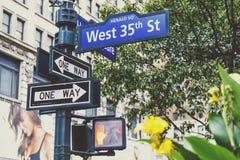 街灯和西部第35路牌有花的a曼哈顿 免版税库存照片