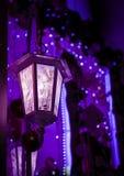 街灯的昏暗的光在紫罗兰色夜 图库摄影
