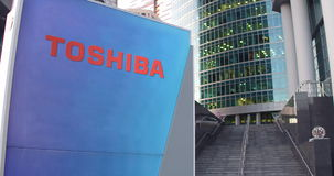 街道与东芝公司商标的标志板 现代办公室中心摩天大楼和台阶背景 社论3D 免版税库存照片