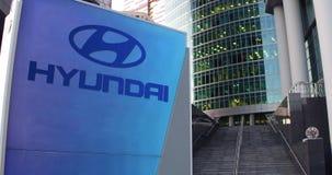 街道与现代汽车有限公司商标的标志板 现代办公室中心摩天大楼和台阶背景 社论 股票录像