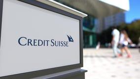 街道与瑞士信贷集团商标的标志板 被弄脏的办公室中心和走的人背景 社论3D 库存照片