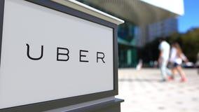 街道与Uber技术公司的标志板 徽标 被弄脏的办公室中心和走的人背景 社论3D 免版税库存照片