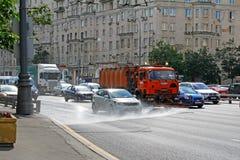 街道乘坐在路的冲洗器机器和车在城市 浇灌的机器洗涤路尘土和土 图库摄影