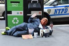 街道叫化子佩带王牌面具和读希拉里・克林顿书什么发生了 库存照片