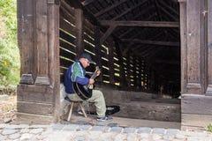 街道吉他演奏员在入口附近弹吉他到隧道,导致Sighisoara老镇在罗马尼亚 库存图片