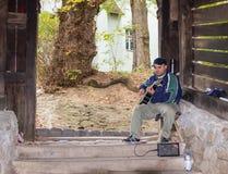 街道吉他演奏员在入口附近弹吉他到隧道,导致Sighisoara老镇在罗马尼亚 免版税库存照片