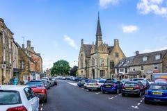 街道和商店在垫木历史的cotswold镇在黄木樨草的 免版税库存图片