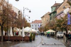 街道咖啡馆和餐馆在Nicolae Balcrscu街道的雨天在锡比乌市在罗马尼亚 图库摄影