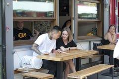 街道咖啡馆生活  坐在桌上的男人和妇女在一份室外菜单,选择食物 库存照片