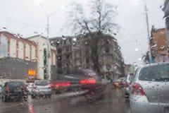 街道在焦点外面的Bokeh光 秋天抽象背景 看法通过与雨下落的车窗 免版税库存照片