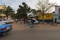 街道场面在市有乘坐自行车和人的一个人的比绍走在一条边路,在几内亚比绍 库存照片