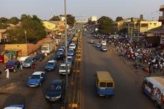街道场面在市比绍在与汽车在大道和人的高峰时间在Bandim市场上,在几内亚比绍 库存照片