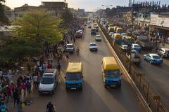 街道场面在市比绍在与汽车在大道和人的高峰时间在Bandim市场上,在几内亚比绍 免版税库存图片