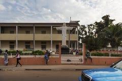 街道场面在走在一个教会前面的一条边路的比绍人城市,在几内亚比绍 库存图片