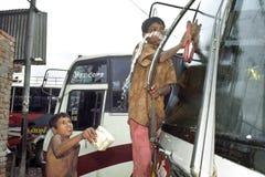 街道孩子擦亮在汽车站达卡的公共汽车 库存照片