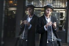 街道帽子和一套严密的衣服的演员魔术师倾斜反对镜子显示 免版税库存照片