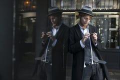 街道帽子和一套严密的衣服的演员魔术师倾斜反对镜子显示 免版税库存图片