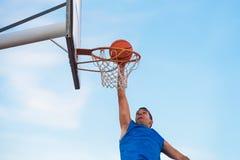街道执行在法院的篮球运动员灌篮 库存照片