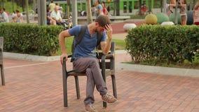 街道执行者在滑稽的姿势坐椅子,在公园的有趣的公众 影视素材