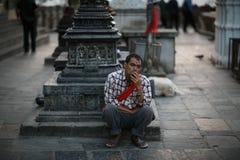 街道抽烟在加德满都街道的布景员  免版税库存图片