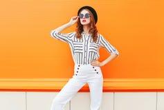 街道时尚妇女模型在五颜六色的桔子的佩带的黑帽会议太阳镜白色裤子 库存图片