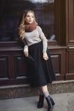 街道时尚概念:摆在窗口的年轻美丽的夫人充分的身体画象  背景秀丽城市生活方式都市妇女年轻人 免版税库存照片