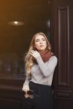 街道时尚概念:摆在窗口的年轻美丽的夫人画象  腰部 背景秀丽城市生活方式都市妇女年轻人 库存图片
