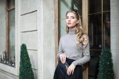 街道时尚概念:摆在门附近的典雅的年轻美丽的妇女画象  腰部 背景秀丽城市生活方式都市妇女年轻人 免版税库存图片