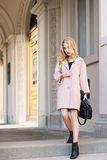 街道时尚概念:穿有提包的年轻美丽的妇女画象桃红色外套走在城市 老 免版税图库摄影