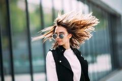 街道时尚概念 年轻美好的模型在城市 美丽的白肤金发的妇女佩带的太阳镜 库存照片