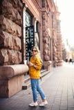 街道时尚的概念 年轻时髦的女学生佩带的boyfrend牛仔裤,白色运动鞋明亮的黄色运动衫 她举行 免版税库存照片