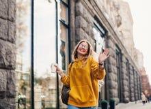 街道时尚的概念 年轻时髦的女学生佩带的boyfrend牛仔裤,白色运动鞋明亮的黄色sweetshot 她举行 免版税库存照片