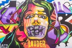 街道显示妇女面孔和词的艺术壁画 免版税库存图片