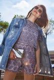 街道样式神色妇女性感的女孩穿戴牛仔布牛仔裤夹克浅黑肤色的男人 库存照片
